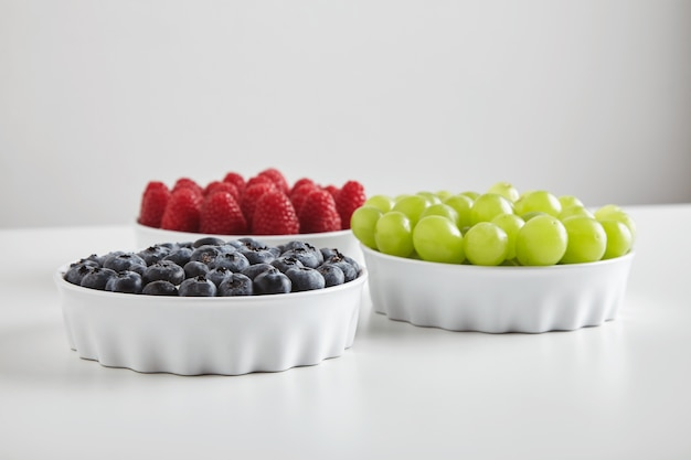 Haufen reifer himbeeren und blaubeeren und grüner kernloser muskat-trauben, genau platziert in keramikschalen, isoliert auf weißem tisch