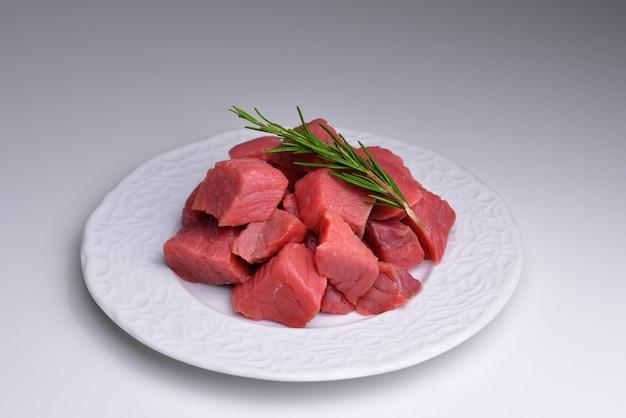 Haufen rindfleischwürfel auf teller frisches rohes, gewürfeltes rotes rindfleischfleisch