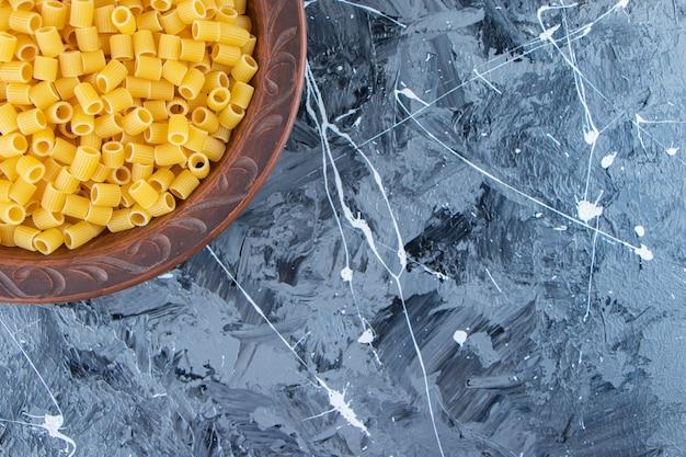 Haufen roher pipetten-rigate-nudeln in einer schüssel auf marmorhintergrund.