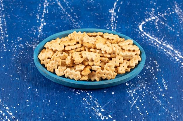 Haufen salziger kleiner cracker auf blauem teller