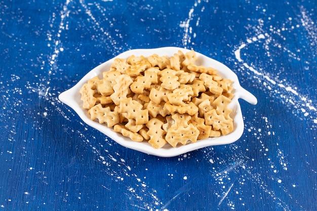 Haufen salziger kleiner cracker auf einem blattförmigen teller.