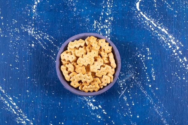 Haufen salziger kleiner cracker in blaue schüssel gelegt.