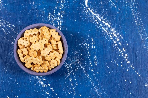Haufen salziger kleiner cracker in blaue schüssel gelegt