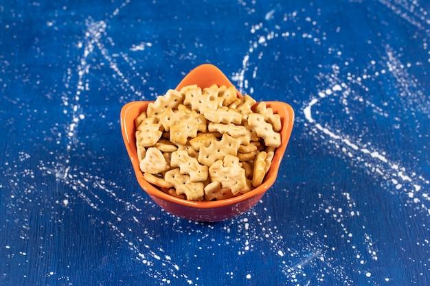 Haufen salziger kleiner cracker in einer orangefarbenen schüssel.