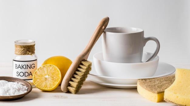Haufen sauberes geschirr und öko-reinigungsprodukte