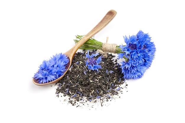 Haufen schwarzer kräutertee-mischung mit kornblumenblättern und frischem blumenstrauß lokalisiert auf weißem hintergrund
