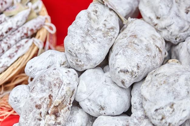 Haufen trockener schinken mit weißem schimmel auf der theke des bauernmarktes