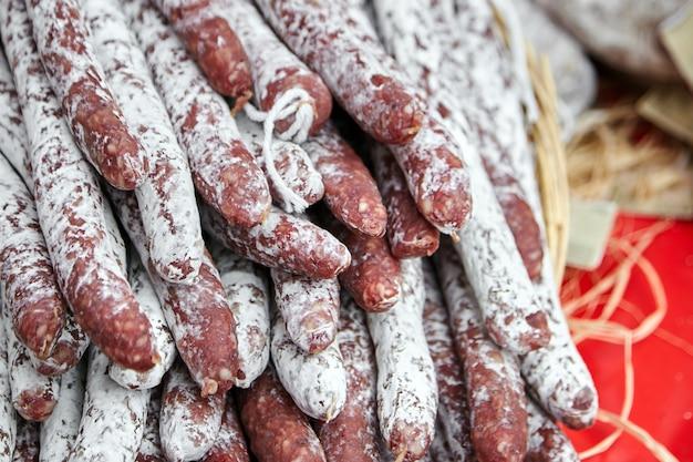 Haufen trockener würste mit weißem schimmel auf der theke des bauernmarktes