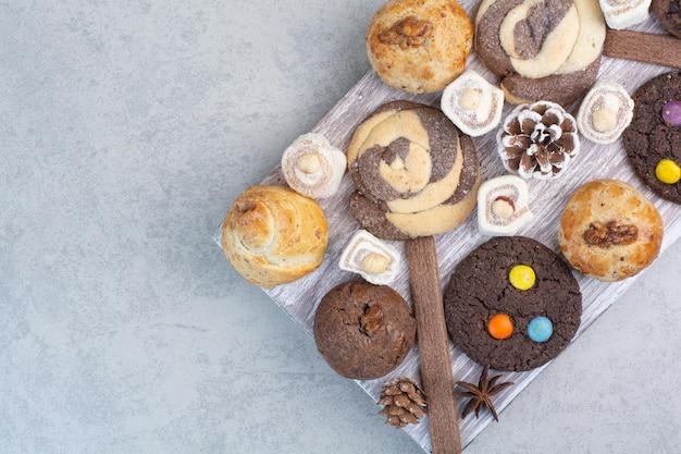 Haufen verschiedener kekse auf holzbrett mit tannenzapfen. foto in hoher qualität