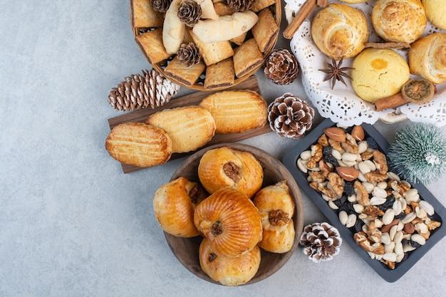 Haufen verschiedener kekse, nüsse und tannenzapfen in schalen. foto in hoher qualität