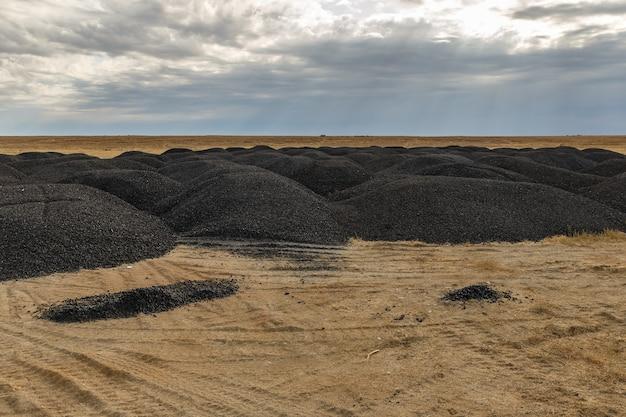 Haufen von altem asphalt in der steppe nach straßenreparatur, kasachstan.