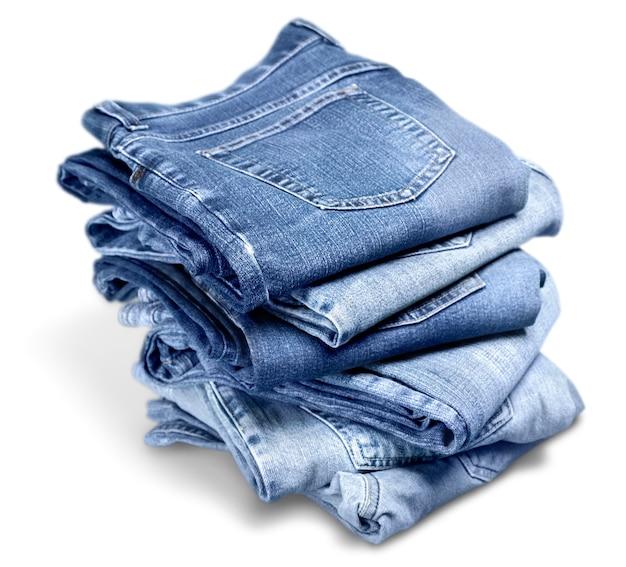 Haufen von blue jeans auf weißem hintergrund