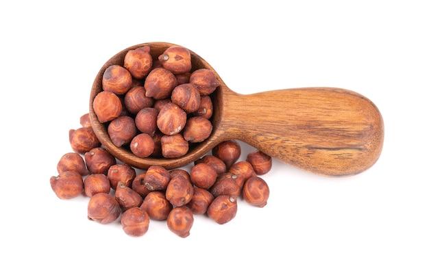 Haufen von braunen kichererbsen in holzlöffel, isoliert auf weißem hintergrund. braune kichererbse. garbanzo, bengal-gramm oder kichererbsenbohne.