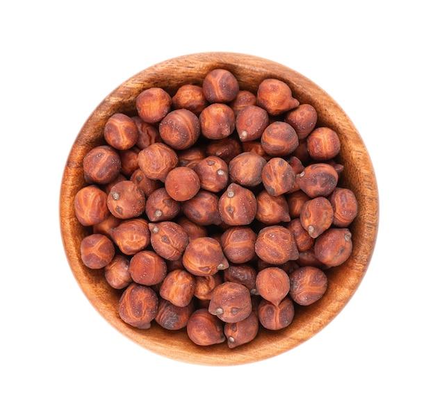 Haufen von braunen kichererbsen in holzschale, isoliert auf weißem hintergrund. braune kichererbse. garbanzo, bengal-gramm oder kichererbsenbohne. ansicht von oben.
