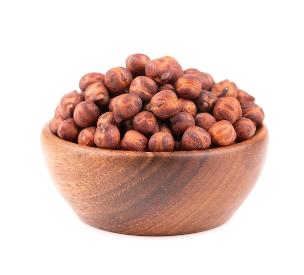 Haufen von braunen kichererbsen in holzschale, isoliert auf weißem hintergrund. braune kichererbse. garbanzo, bengal-gramm oder kichererbsenbohne.