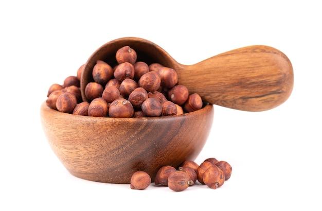 Haufen von braunen kichererbsen in holzschale und löffel, isoliert auf weißem hintergrund. braune kichererbse. garbanzo, bengal-gramm oder kichererbsenbohne.