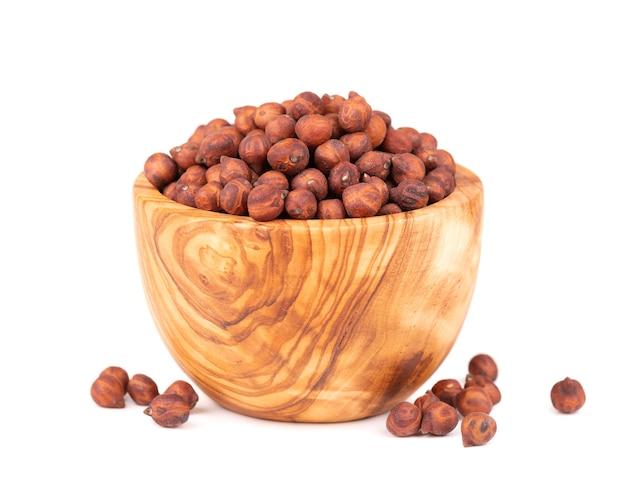 Haufen von braunen kichererbsen in olivenschale, isoliert auf weißem hintergrund. braune kichererbse. garbanzo, bengal-gramm oder kichererbsenbohne.