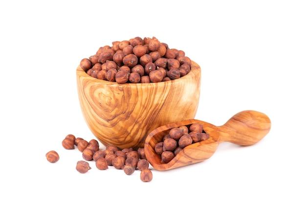 Haufen von braunen kichererbsen in olivenschale und schaufel, isoliert auf weißem hintergrund. braune kichererbse. garbanzo, bengal-gramm oder kichererbsenbohne.