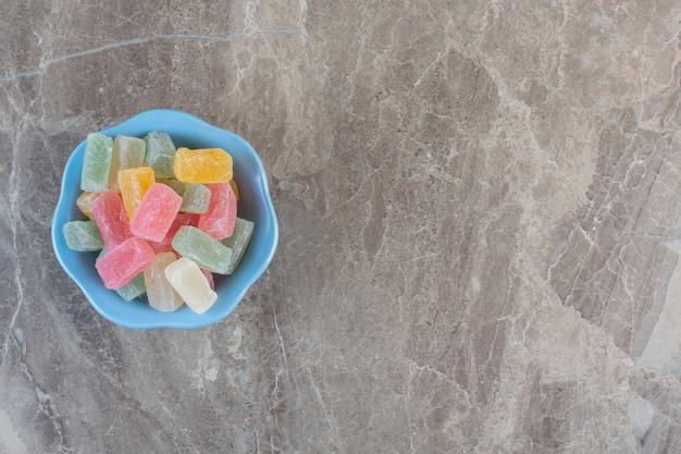 Haufen von bunten bonbons in blauer schüssel. draufsicht über grauem hintergrund.