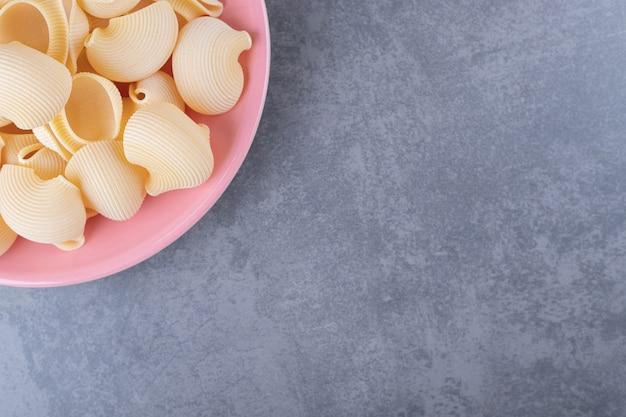 Haufen von conchiglie-nudeln auf rosa teller.