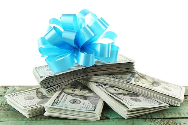 Haufen von dollar mit schleife als geschenk isoliert auf weißer oberfläche