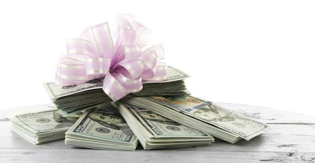 Haufen von dollars mit schleife als geschenk isoliert auf weiß