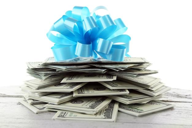 Haufen von dollars mit schleife als geschenk isoliert auf weißer oberfläche