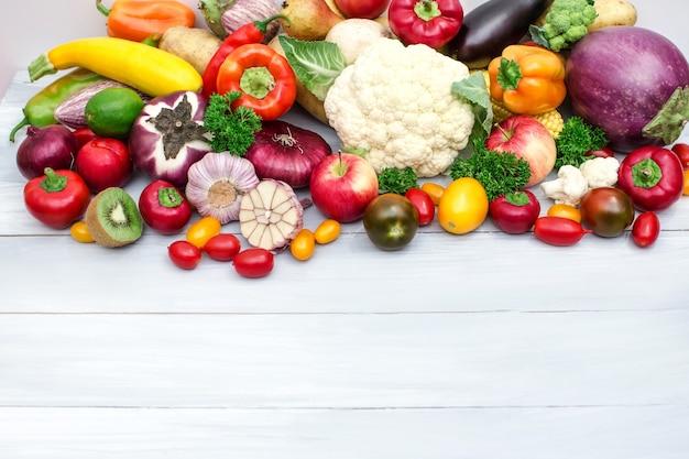 Haufen von frischem obst und gemüse auf hölzernem hintergrund.
