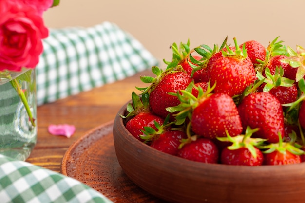 Haufen von frischen erdbeeren in der keramischen schüssel auf rustikalem hintergrund