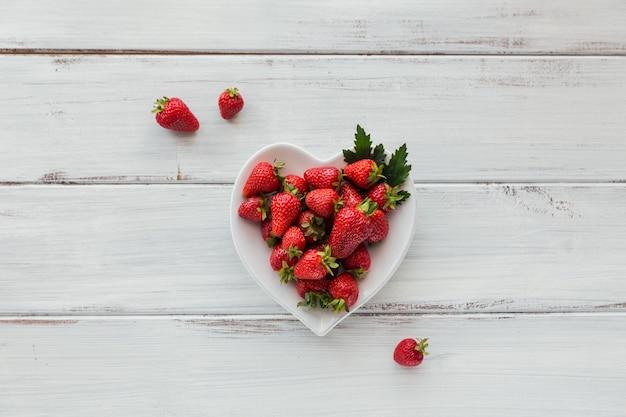 Haufen von frischen erdbeeren in einer herzformkeramikschale auf weißem hölzernem hintergrund