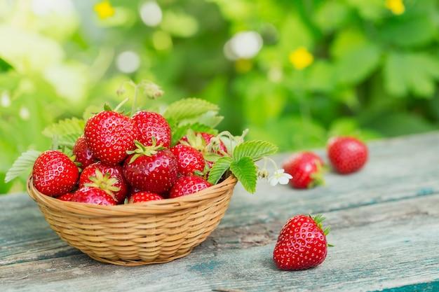 Haufen von frischen erdbeeren in einer korbschale auf rustikalem hölzernem hintergrund
