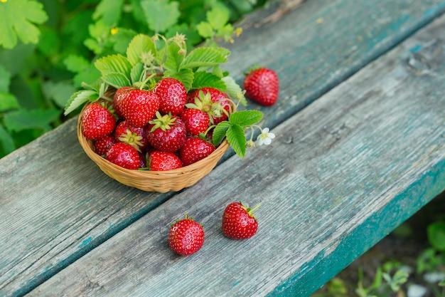 Haufen von frischen erdbeeren in korbschale auf rustikaler holzwand. gesundes essen und diätnahrungskonzept.