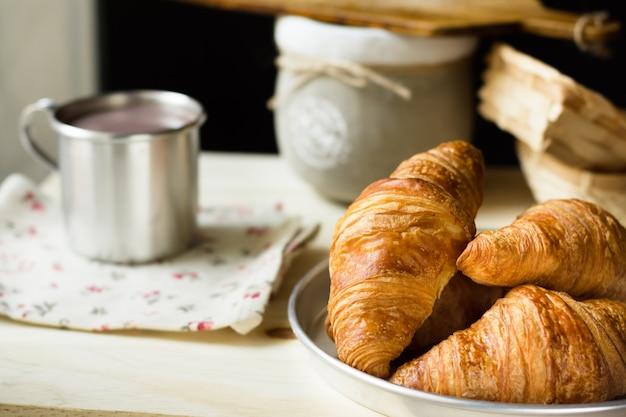 Haufen von frischen hörnchen mit goldkruste, becher mit heißem kakao oder schokolade, rustikaler hölzerner küchentisch