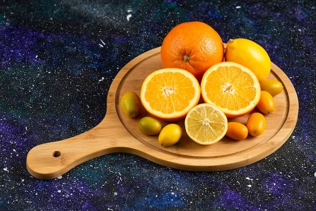 Haufen von frischen zitrusfrüchten auf holzbrett. ganz oder halb geschnitten.
