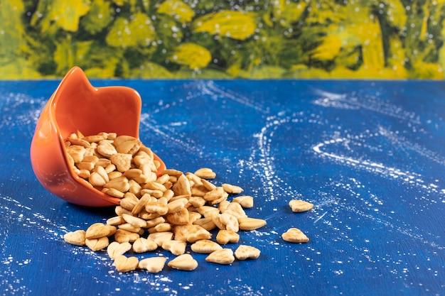 Haufen von gesalzenen herzförmigen crackern aus orangefarbener schüssel.