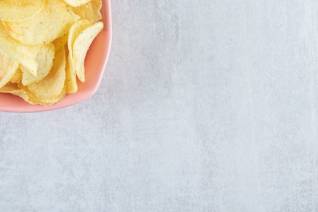 Haufen von gesalzenen knusprigen chips in rosa schüssel auf stein gelegt.