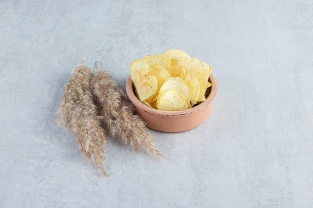Haufen von gesalzenen knusprigen chips in schüssel auf stein gelegt.