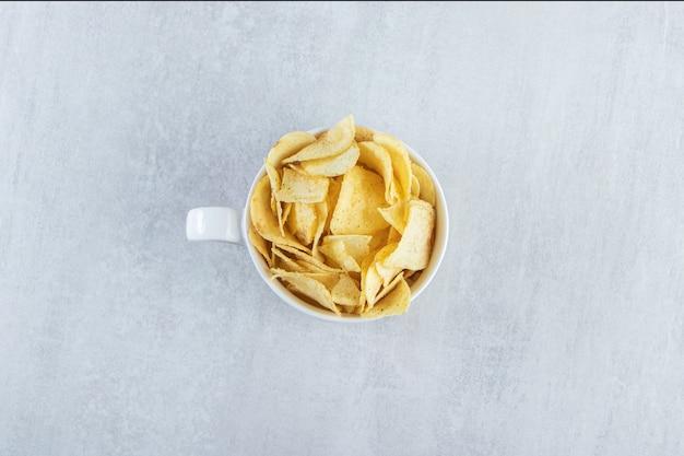 Haufen von gesalzenen knusprigen chips in tasse auf stein gelegt.