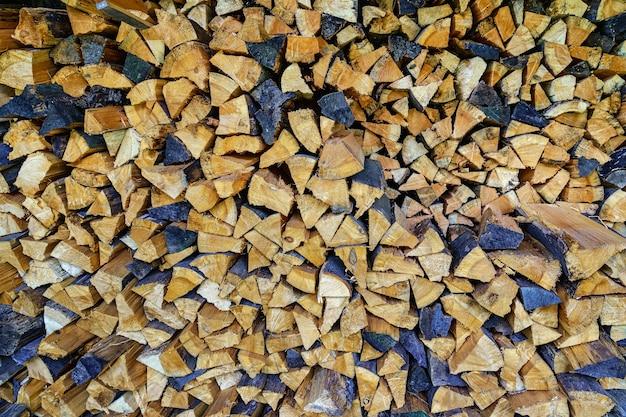 Haufen von geschnittenem und gestapeltem brennholz in verschiedenen farben. hintergrund.
