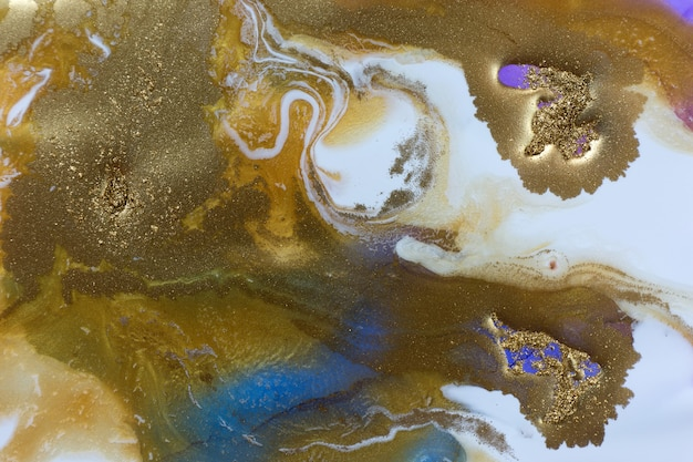 Haufen von goldenen pailletten auf weißen und blauen flecken des abstrakten hintergrundmusters der farbe