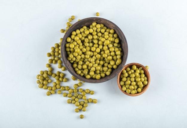 Haufen von grünen erbsen in schüssel und tisch.