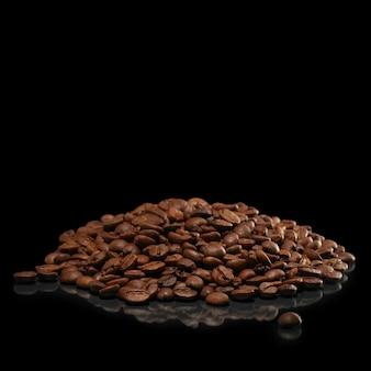 Haufen von kaffeebohnen mit reflexion auf schwarzer oberfläche