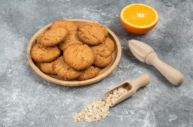 Haufen von keksen auf holzbrett. halb geschnittene orange mit haferflocken über grauem tisch.