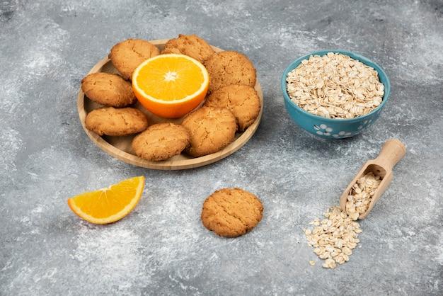 Haufen von keksen mit orange auf holzbrett und haferflocken in einer schüssel.