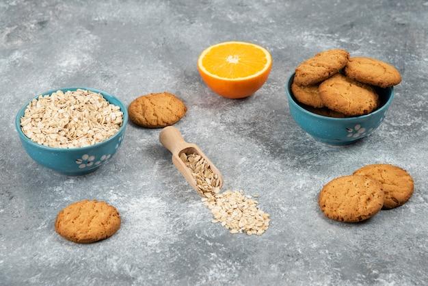 Haufen von keksen und haferflocken in einer schüssel und halbgeschnittener orange über grauer oberfläche.