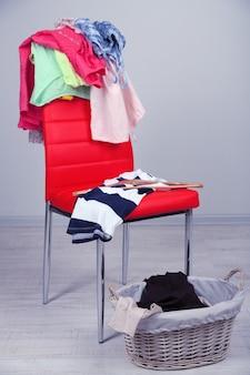 Haufen von kleidern auf farbstuhl, auf grauem hintergrund
