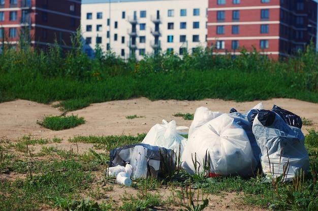 Haufen von müllpaketen auf einem boden gegen unscharfes mehrfamilienhaus. plastikmüll. konzept für müllrecycling und abfallentsorgung.