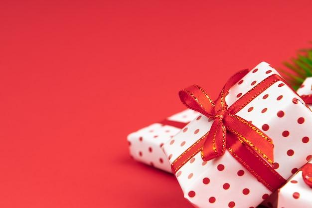 Haufen von neujahrsgeschenken, eingewickelt in geschenkpapierpolka mit festlichem band auf rot