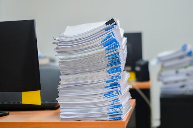 Haufen von papierarbeitsstapeldokumenten auf schreibtisch