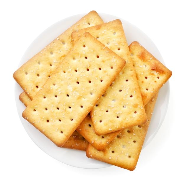 Haufen von salzigen crackern in einem teller auf weißem hintergrund, isoliert. ansicht von oben